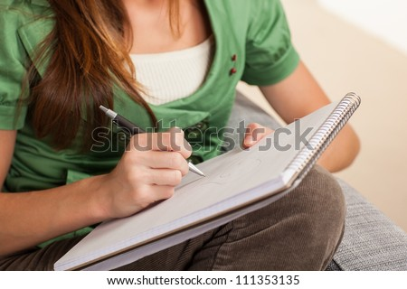 Beautiful young female sitting on gray chair writing on pad of paper.