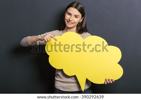 Beautiful young female student is holding a yellow speech bubble, pointing on it and smiling, standing against blackboard - stock photo