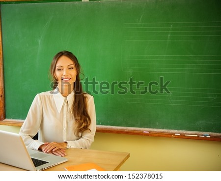 Beautiful young female teacher with laptop behind desk near blackboard