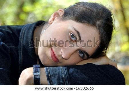 Beautiful young female teen rests her head on her arms while enjoying the solitude of an outdoor park. - stock photo