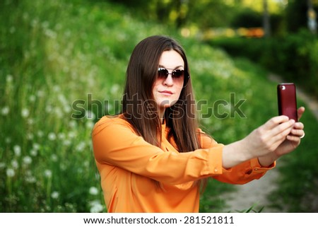 Beautiful young female tourist takes travel selfie. Cute smiling young caucasian teenage girl taking a selfie outdoors on sunny summer day. - stock photo