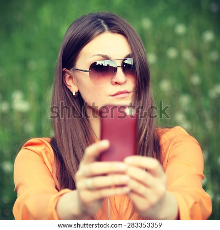 Beautiful young female tourist takes travel selfie. Cute smiling young caucasian teenage girl taking a selfie outdoors on sunny summer day. Photo toned style Instagram filters. - stock photo