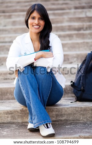 beautiful young female university student sitting outdoors - stock photo
