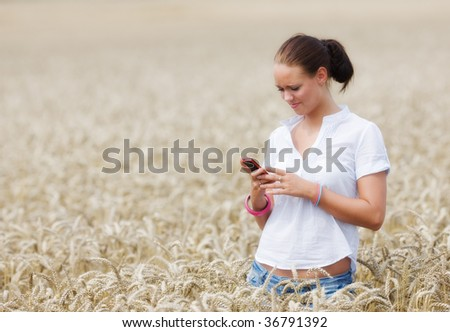 Beautiful young female using her mobile phone - stock photo