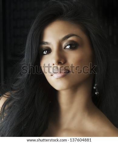 Beautiful young female with exotic eyes and straight long back hair - stock photo