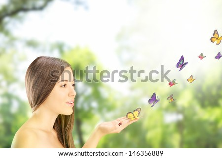 Beautiful young female with many colorful butterflies on her hand, posing outside in a park - stock photo