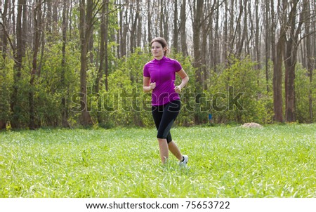 Beautiful young fit girl running outdoors in the meadow - stock photo