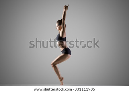 Beautiful young fit woman in sportswear doing sport exercise for shoulders, ankles, thighs, calves and spine, standing in variation of Chair Posture, utkatasana, full length, studio, gray background