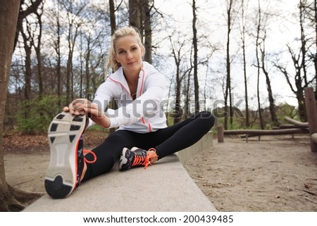 Beautiful young fitness female stretching before running in park. Caucasian woman exercising in nature.