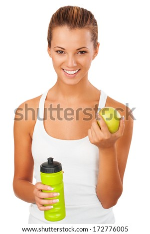 Beautiful young fitness woman happy smiling holding apple and water bottle. Healthy lifestyle photo of Caucasian fitness model isolated on white background. - stock photo