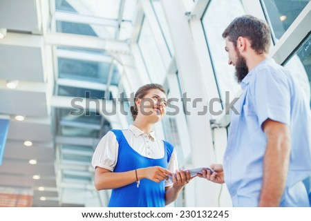Beautiful young flight attendant checking documents of male tourist - stock photo