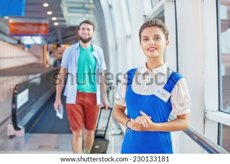 Beautiful young flight attendant in the airport (tourist walking on a background) - stock photo