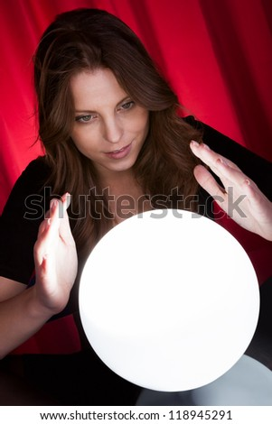 Beautiful young fortuneteller holding her hands around a glowing ball as she foretells the future and what it holds - stock photo