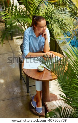 Beautiful Young Freelancer Woman Using Laptop Computer Sitting At Cafe Table. Happy Smiling Girl Working Online Or Studying And Learning While Using Notebook. Business People Working Outdoors. - stock photo