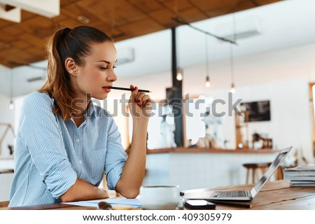 Beautiful Young Freelancer Woman Using Laptop Computer Sitting At Cafe Table. Happy Smiling Girl Working Online Or Studying And Learning While Using Notebook. Freelance Work, Business People Concept   - stock photo