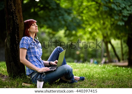 Beautiful young freelancer woman using laptop sitting on the grass in the park.Happy smiling girl working on line.Studying and learning using notebook computer.Freelance work,business people concept.