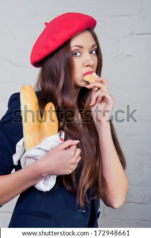 Beautiful young Frenchwoman in a red beret eating baguette - stock photo
