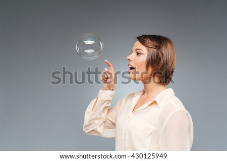 Beautiful young funny girl playing with bubbles isolated on the gray background