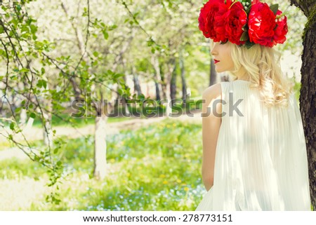 beautiful young gentle elegant young blond woman with red peony in a wreath of white blouse walking in the lush apple orchard - stock photo