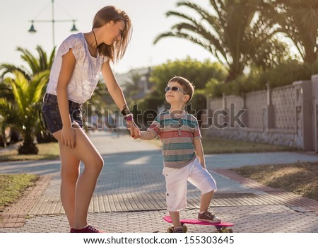Beautiful young girl and cute kid walking with a skateboards outdoor on summer - stock photo
