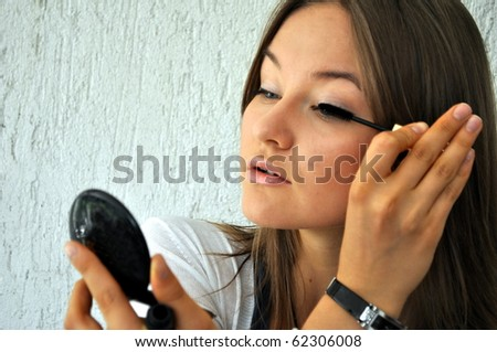 Beautiful young girl applying her make up - stock photo