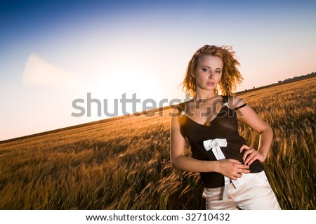 Beautiful young girl at gold field - stock photo