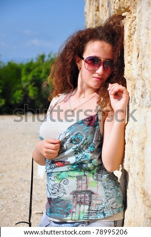 Beautiful young girl at the background of an ancient fortress