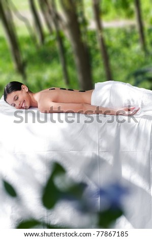 Beautiful young girl at the day spa with black stones on her bare back - stock photo
