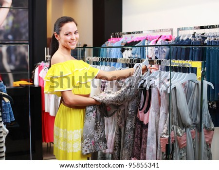 Beautiful young girl at the store chooses to purchase clothing - stock photo