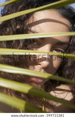 Beautiful young girl behind leaves with her sexy eyes open - stock photo