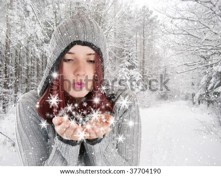 Beautiful young girl blowing snowflakes in white winter forest covered with snow - stock photo