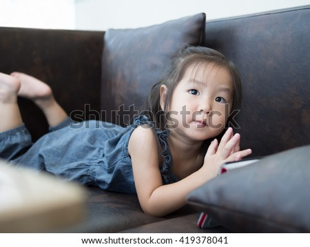 Beautiful young girl child laying down on a sofa at home ,  asian girl - stock photo