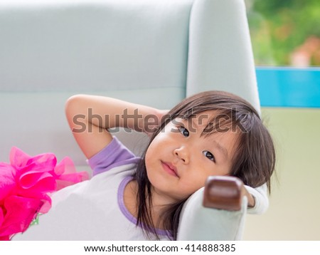 Beautiful young girl child laying down on a white sofa at home, asian girl - stock photo
