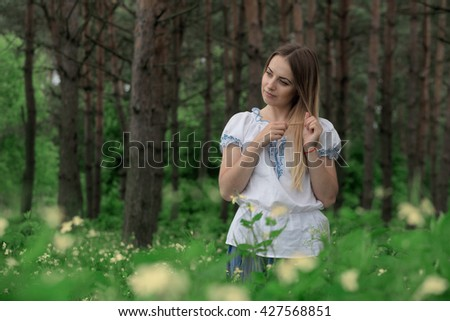 Beautiful young girl close-up in a white shirt, against a background of green forest.