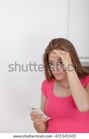 Beautiful young girl communicates via a mobile phone. Receives a disturbing message. - stock photo