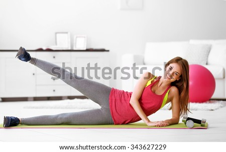 Beautiful young girl doing exercises at home - stock photo