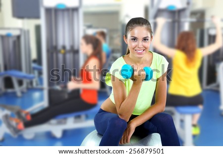 Beautiful young girl doing exercises in gym - stock photo