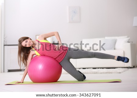 Beautiful young girl doing exercises with fit ball at home - stock photo