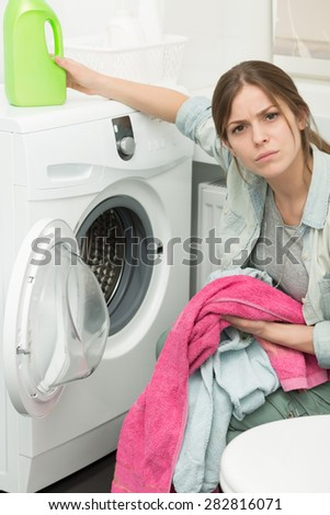 Beautiful young girl doing laundry at home