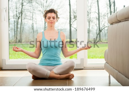Beautiful young girl doing yoga exercise in front of the window. Indoor. - stock photo