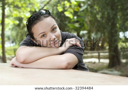 Beautiful young girl dreaming in the park - stock photo