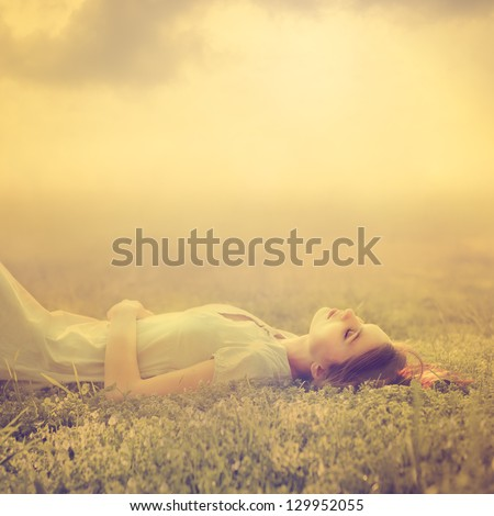 beautiful young girl dreams of lying on a magic meadow in spring - stock photo
