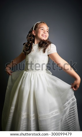 Beautiful young girl dressed in white, dancing like a princess. First Communion. Perfect teeth and smile, long curly hair. Dark background, studio shoot. - stock photo