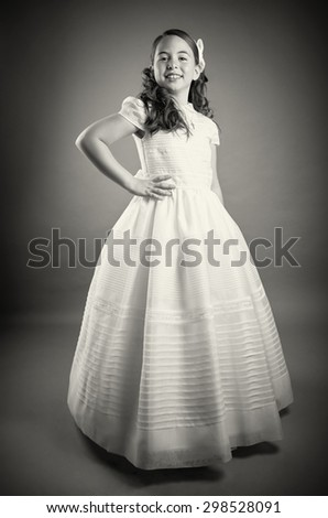 Beautiful young girl dressed in white. First Communion, full length. Perfect teeth and smile, long curly hair, hand on hips. Dark background, studio shoot. Black & white picture. - stock photo