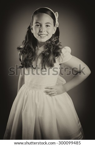 Beautiful young girl dressed in white. First Communion. Perfect teeth and smile, long curly hair, hand on hips. Dark background, studio shoot. Sepia picture. - stock photo