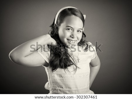 Beautiful young girl dressed in white. First Communion. Perfect teeth and smile, long curly hair, hand in hair. Dark background, studio shoot. Sepia picture. - stock photo