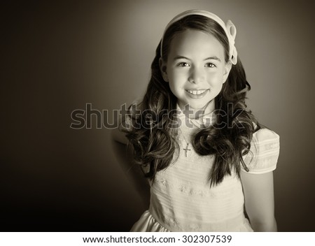 Beautiful young girl dressed in white. First Communion. Perfect teeth and smile, long curly hair, hands on hips. Dark background, studio shoot. Sepia picture. - stock photo