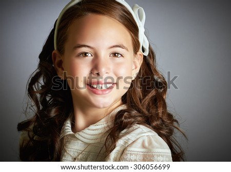 Beautiful young girl dressed in white. First Communion. Perfect teeth and smile, long curly hair. Dark background, close up studio shoot. - stock photo