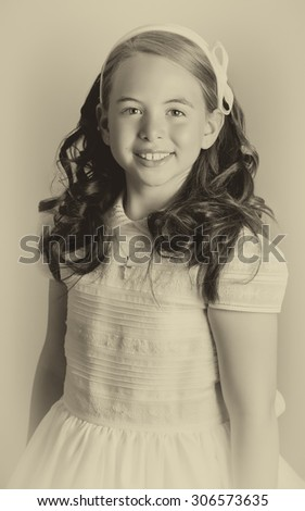 Beautiful young girl dressed in white. First Communion. Perfect teeth and smile, long curly hair. Dark background, studio shoot. Sepia picture. - stock photo
