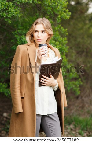 Beautiful young girl drink coffee in blossom garden on a spring day - stock photo